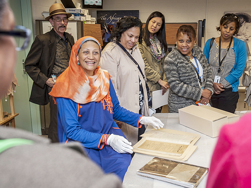 ACM Registrar Habeebah Muhammad gives visitors a look at objects from the Plummer Family Collection.