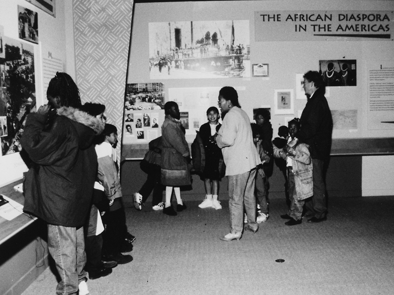 Visitors view the exhibition Black Mosaic: Race Color and Ethnicity Among Black Immigrants in Washington, DC.