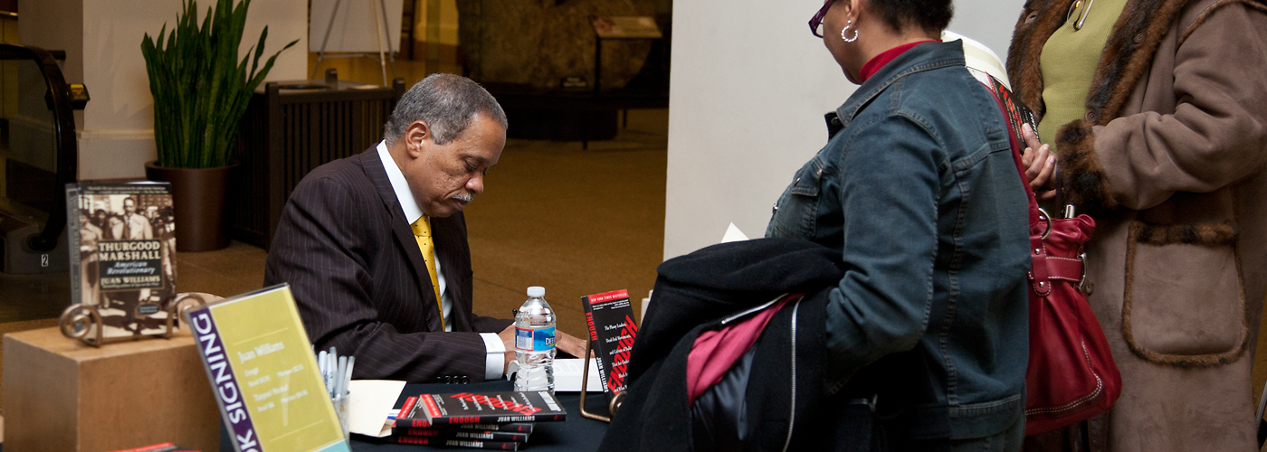 Journalist Juan Williams signs books for participants at the annual Martin Luther King Jr. Program, 2009.