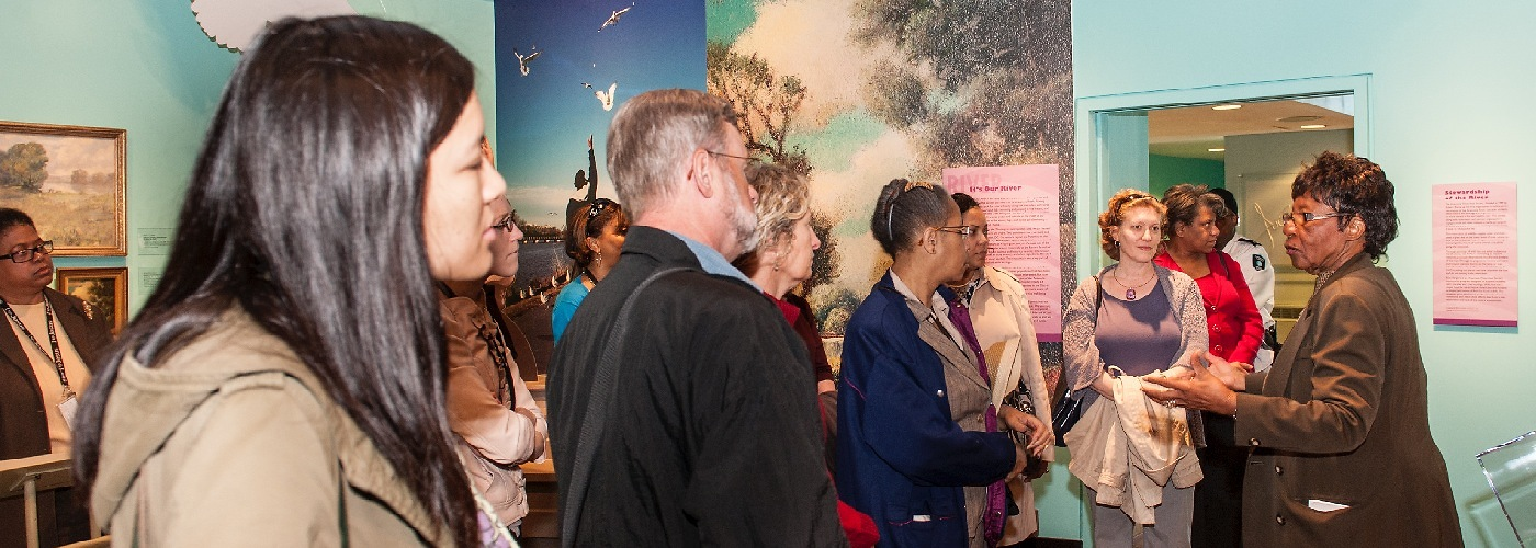 Docent Geraldine Whitley gives a tour of the exhibit Reclaiming the Edge: Urban Waterways and Civic Engagement.