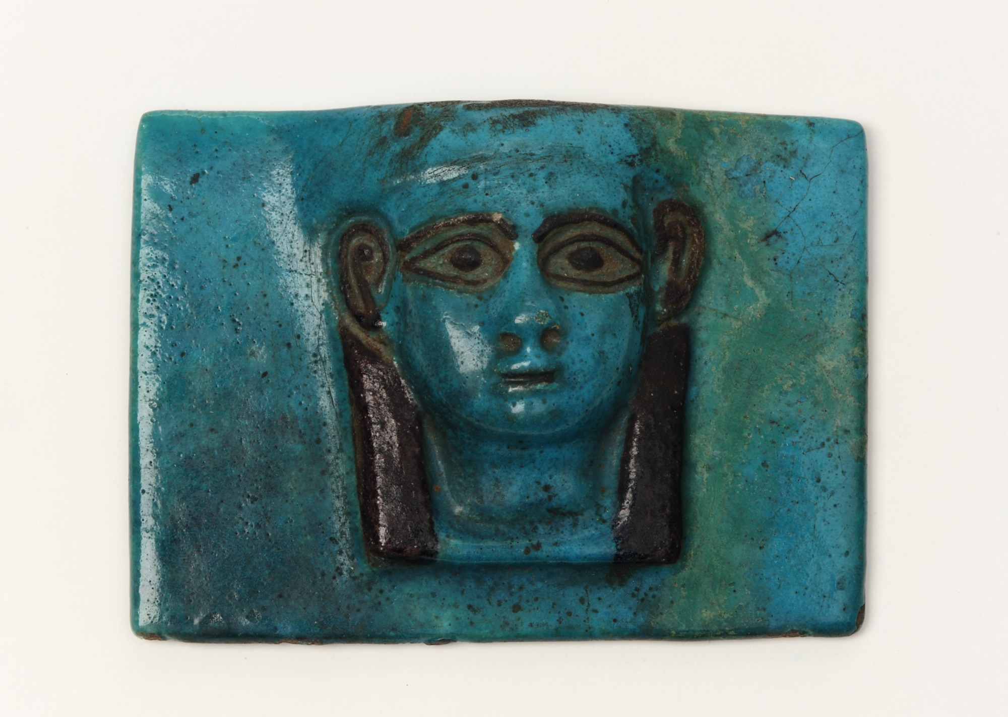 Thin oblong tile, with a female head in relief