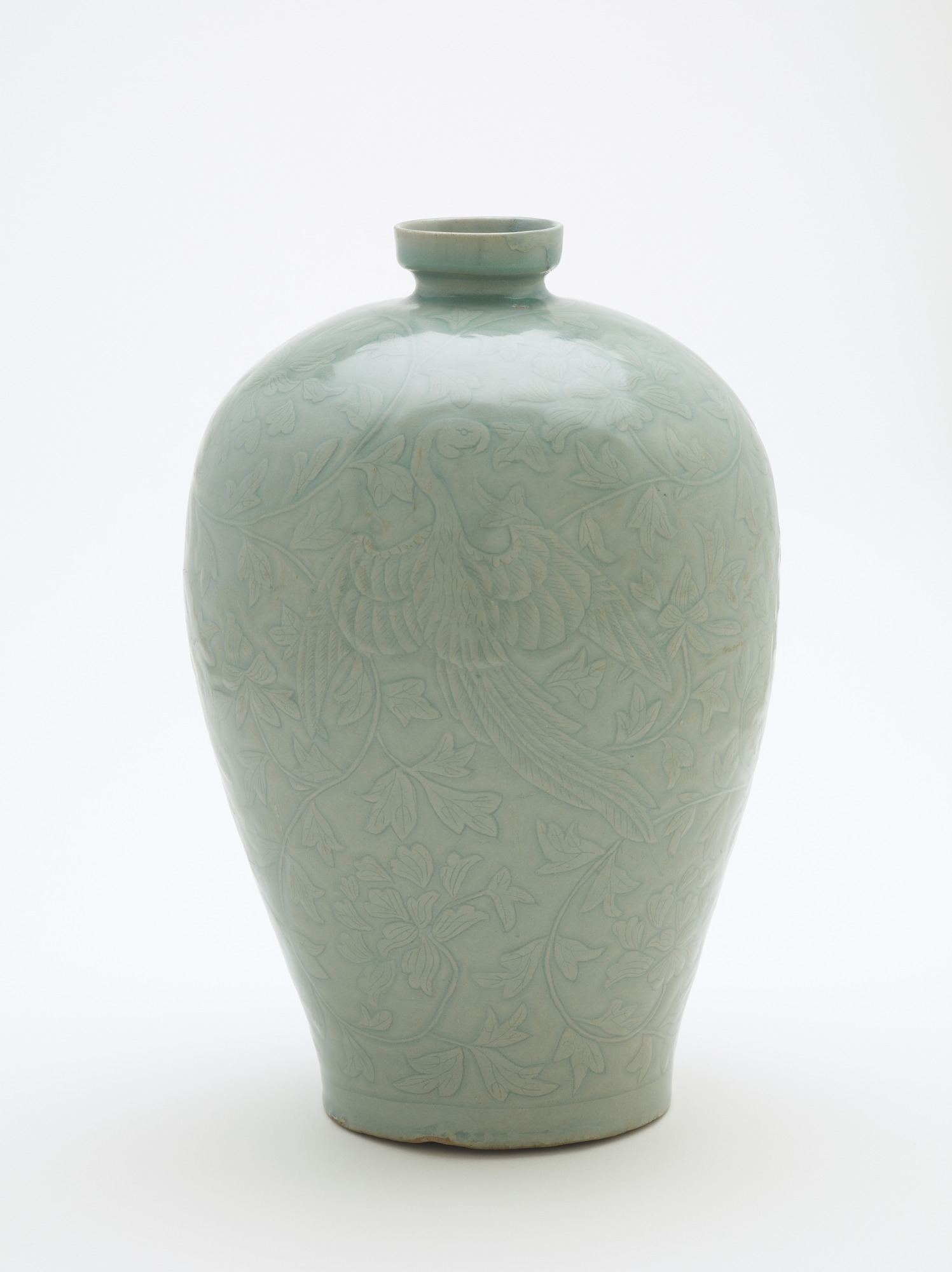 Bottle with carved and incised design of two phoenixes and peony vinescrolls, profile
