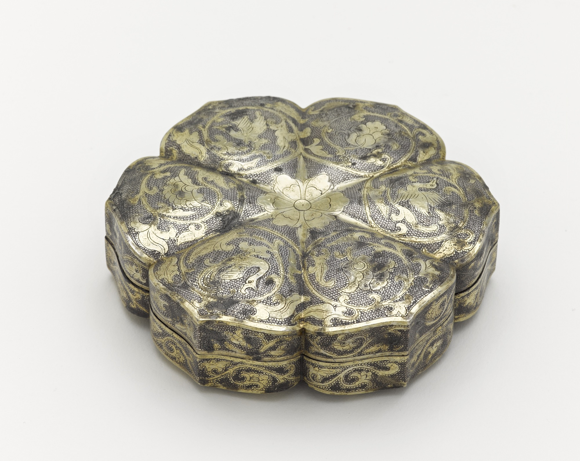 3/4 profile: Covered box in the form of a six petalled flower with birds and floral scrolls