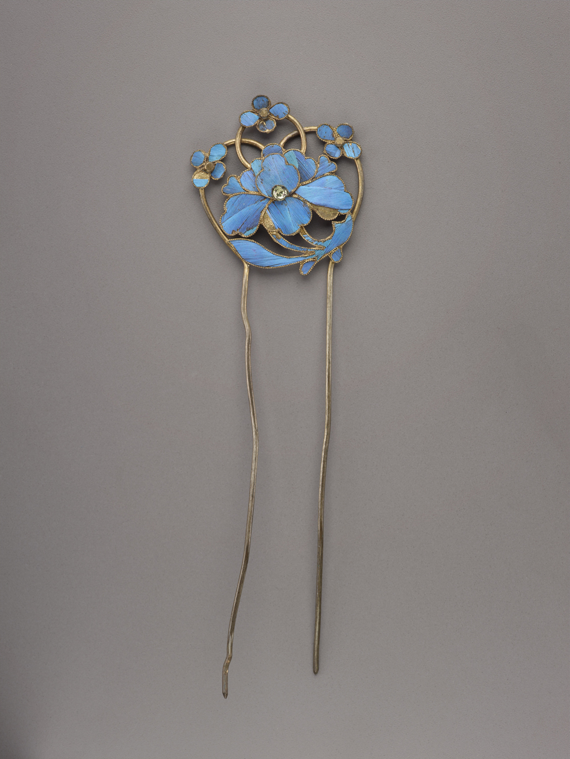 Double-prong kingfisher feather hairpin with floral motif.
