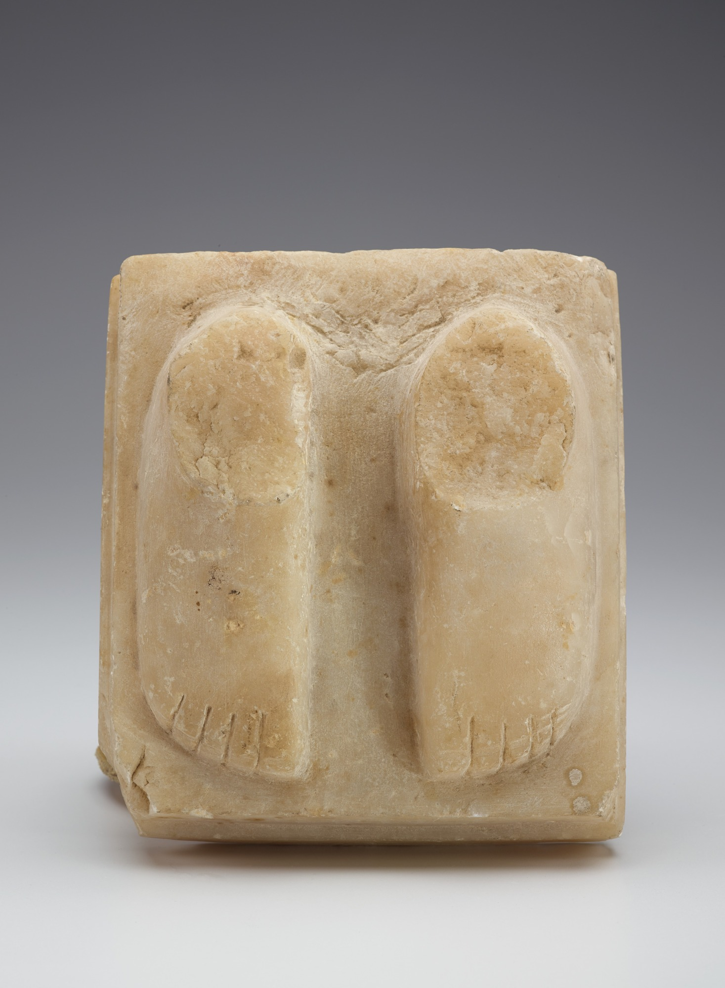 Stepped base with pair of feet from a figure, fragment