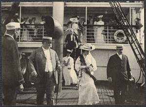 Alice Roosevelt wearing a lei beside William Taft, on deck of the SS Manchuria, upon their arrival to Hawaii.