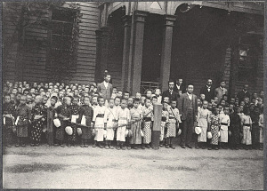 Japanese children and others standing along carriage route
