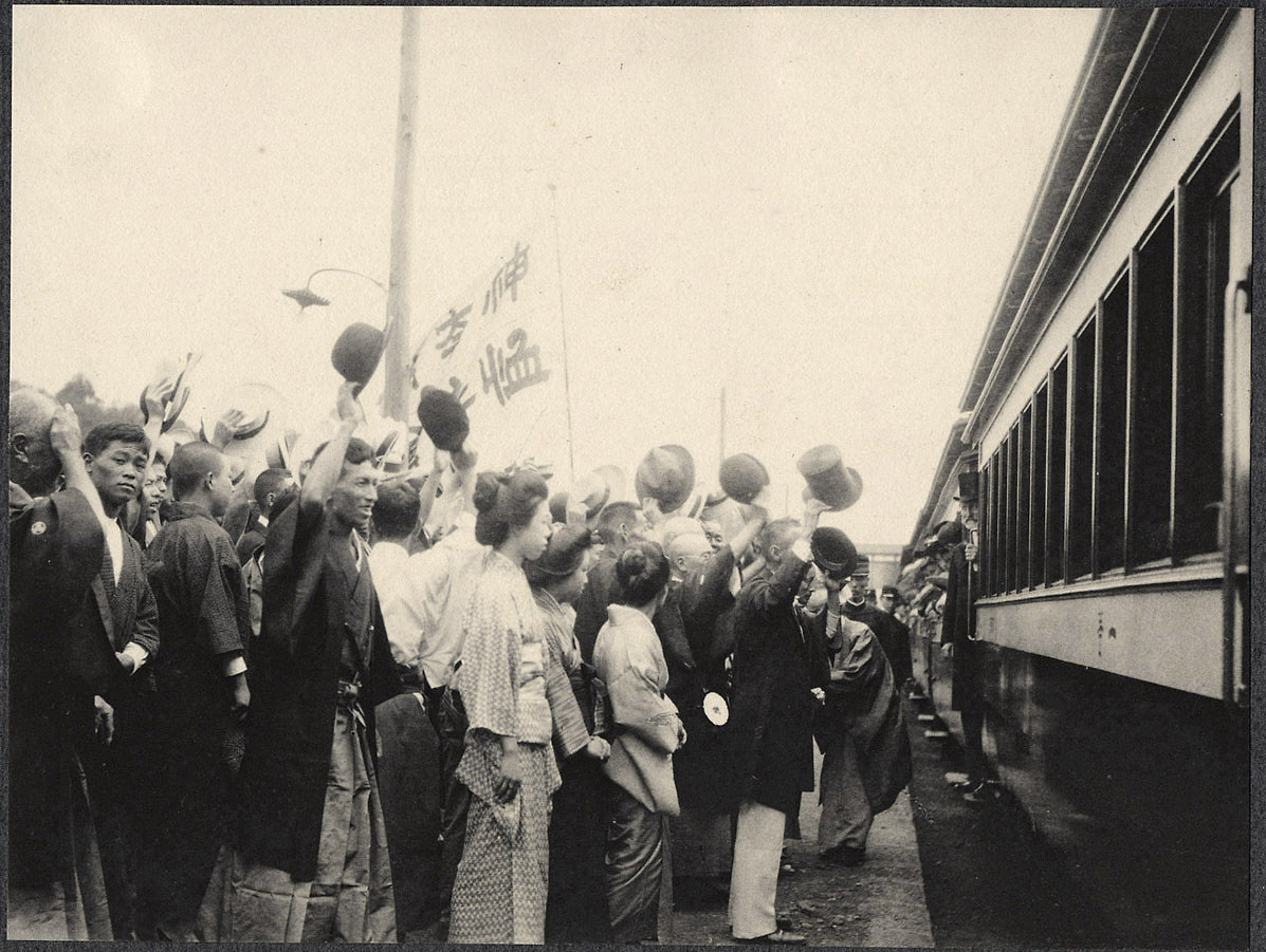Japanese crowds wave to a train carriage enroute from Yokohama to Tokyo