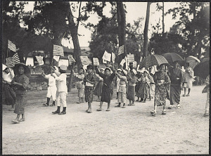 Japanese children parading with American and Japanese flags