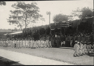 Manila: Group of American soldiers with banner march before viewing stand