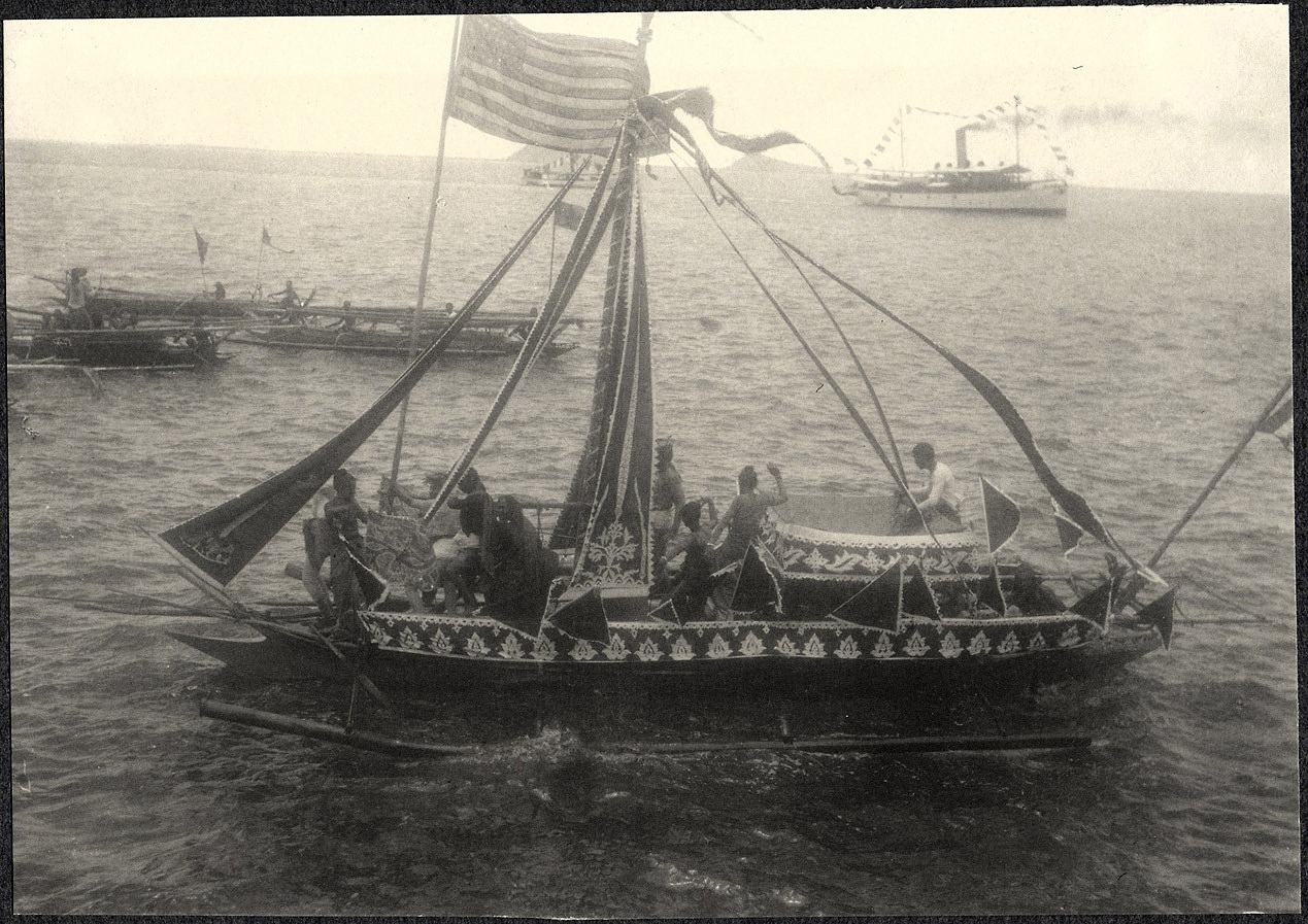 Zamboanga: decorated banca with American flag, from the deck of the USS Logan