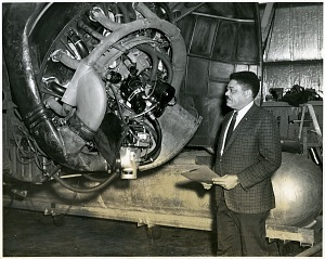 "Photograph of Lawrence Edward ""Larry"" Campbell, Jr. next to an observatory telescope."