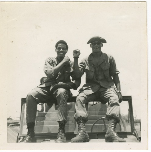 Photograph of two American soldiers sitting on a jeep in