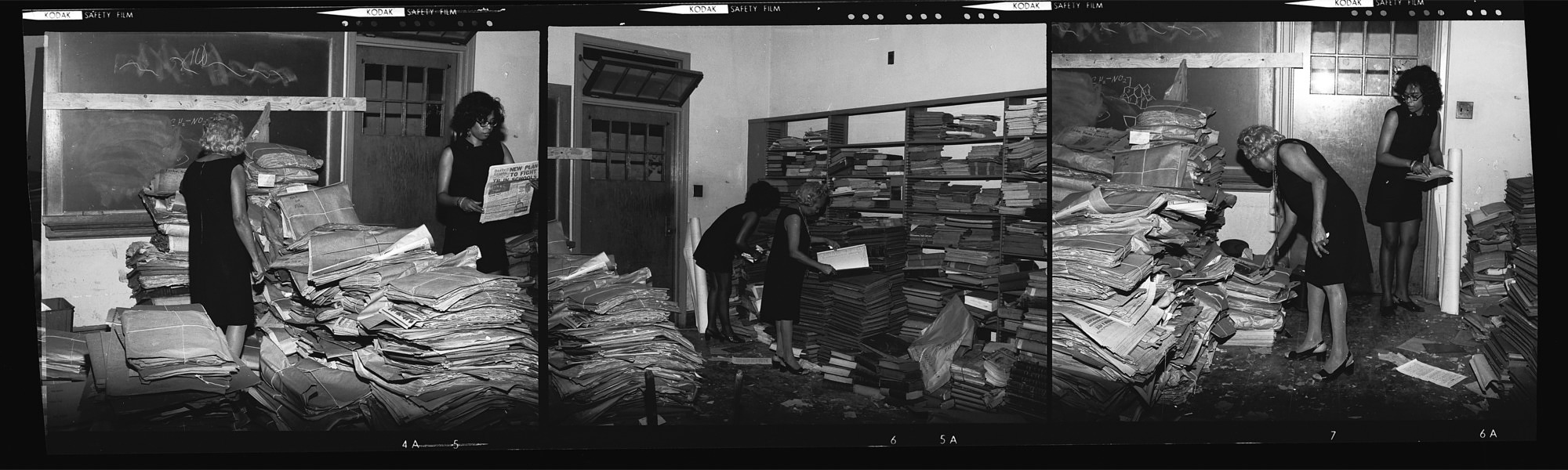 Women working with newspapers and man microfilming newspapers