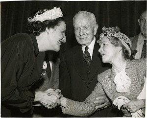 Photograph of Dorothy Shaver shaking hands with another man and woman at the 1948 American Design Awards.