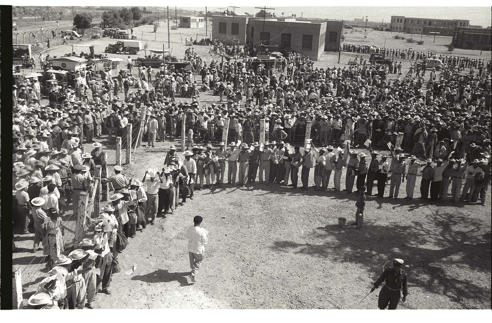 Supervised by an armed guard braceros wait in line to be processed through the Monterrey Processing Center, Mexico while others wait outside the barbed wire enclosure.