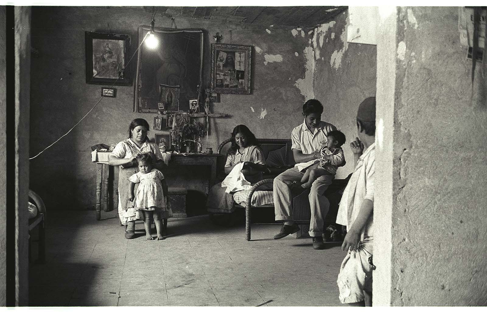 Women framed by an arch work and care for children in their San Mateo, Mexico, bracero family home.