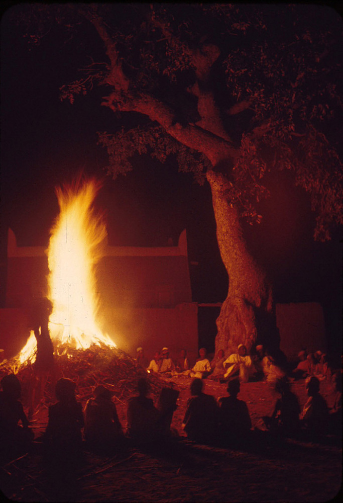 Children studying the Koran as they sit around a fire, Shika, Nigeria. slide