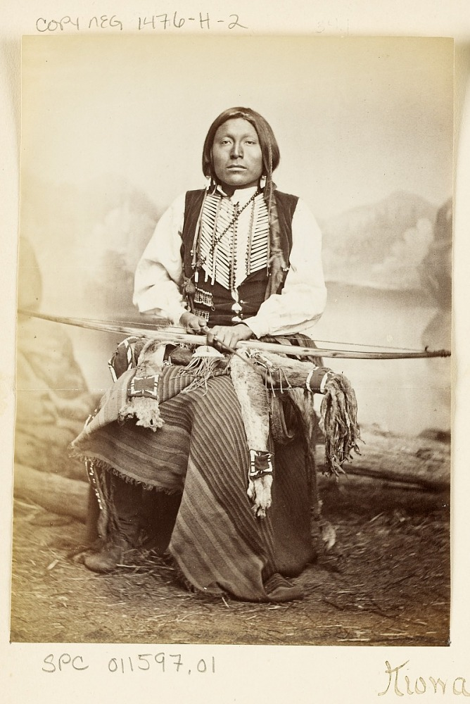 Portrait of Man in Partial Native Dress, Wearing Blanket And Hairpipe Breastplate and Holding Bow and Arrow with Fur And Beadwork Quiver 1867-75