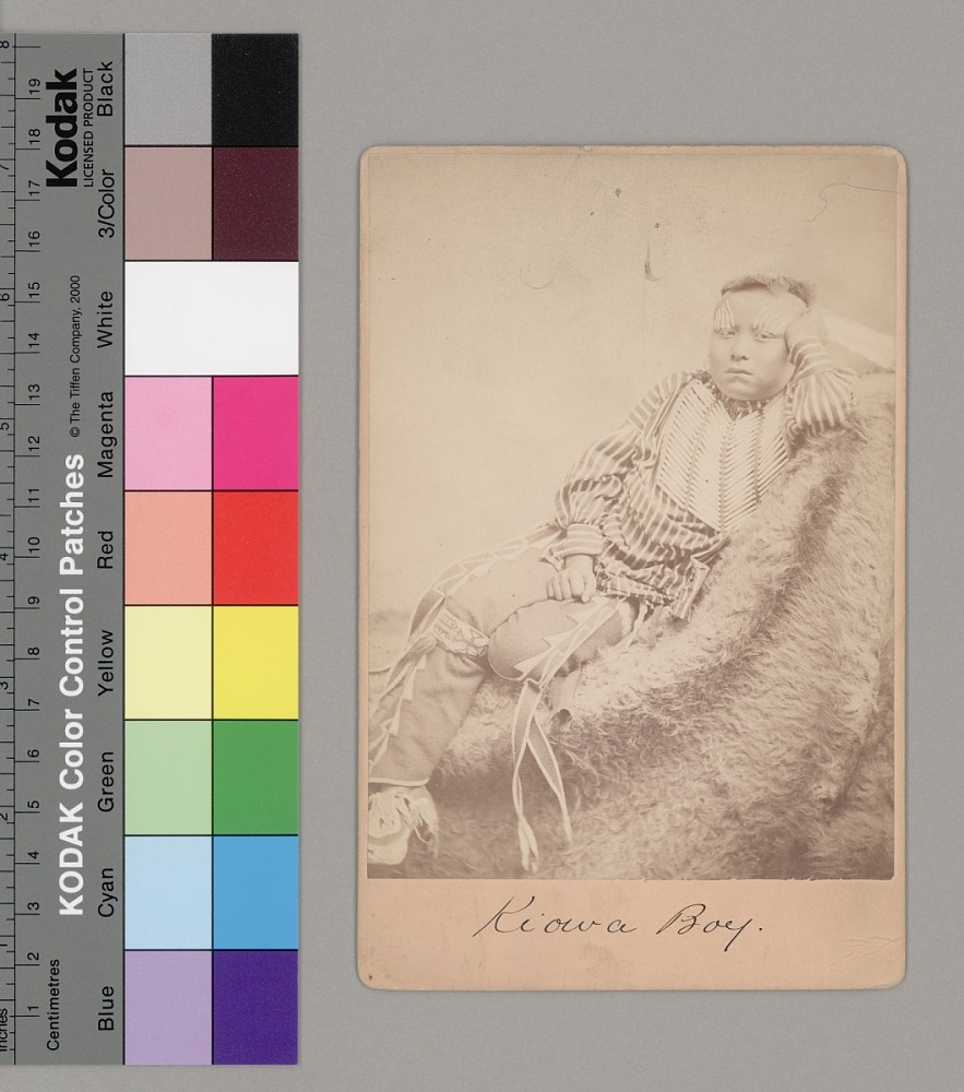 Portrait of Tar-Lo, Boy, with Face Paint, Hairpipe Breastplate, and in Partial Native Dress, Lying on Animal Skin Near Fort Sill. 1867-75