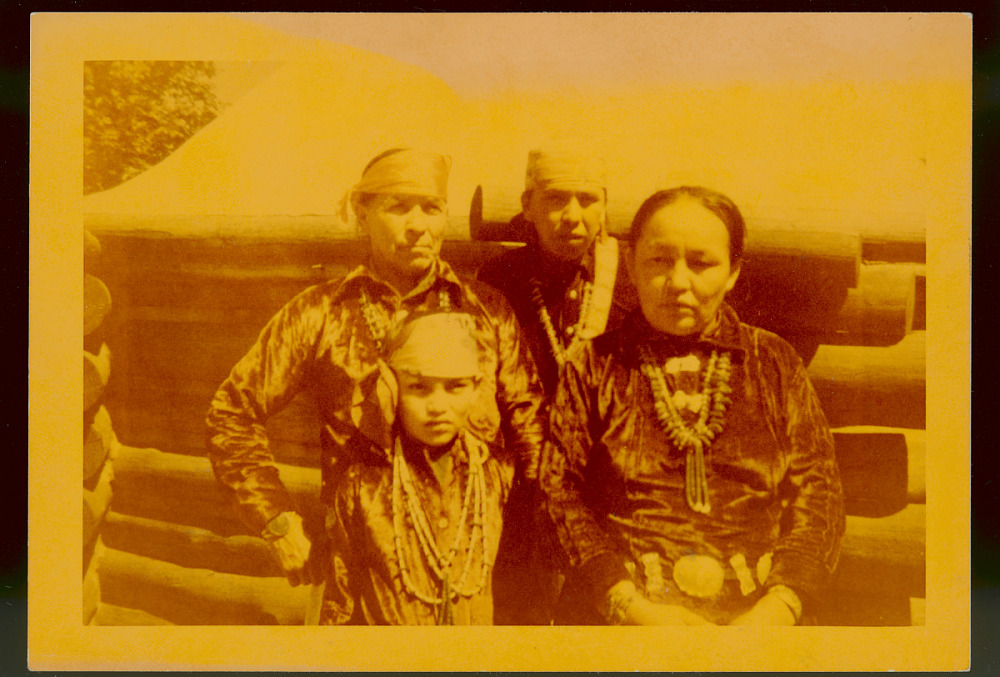 Charley, Dry Painter, with Wife and Two Sons in Native Dress Outside Log Cabin at Railroad Fair 1952