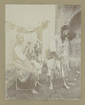 Two Men in Costume; One, Dancer; Other Musician Playing Kissar Near Carved Wooden Panel and Mud-Brick Archway 1860
