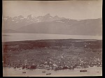 Elevated view of town and port with snow-covered mountains and islands in distance 1892