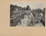 Ruins of Borobudur, Buddhist Monument (9th Century AD), Fourth Terrace, Gandavyuha-Sutra Stone Bas Reliefs Depicting Pilgrimage of Sudhana, Stupas (Reliquaries) and Exposed Seated Buddhas; Two Men in Costume, One with Umbrella Nearby; Village in Distance 1902