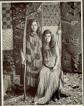 Portrait of Two Young Women, One Wearing Flax-Fiber Cloak With Taniko Border; Other Holding Carved and Painted Wood Paddle; Both Near Carved Wood Ancestor Panels Interwoven with Reedwork Panels 1900