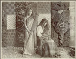 Two Young Women in Costume, One Wearing Flax-Fiber Cloak And Holding Wood Paddle with Carved Designs Near Carved Wood Ancestor Panels Interwoven with Reedwork Panels 1900