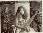 Portrait of Young Woman Wearing Flax-Fiber Dress and Holding Carved Wood Paddle Near Carved Wood Ancestor Panels Interwoven with Reedwork Panels 1900