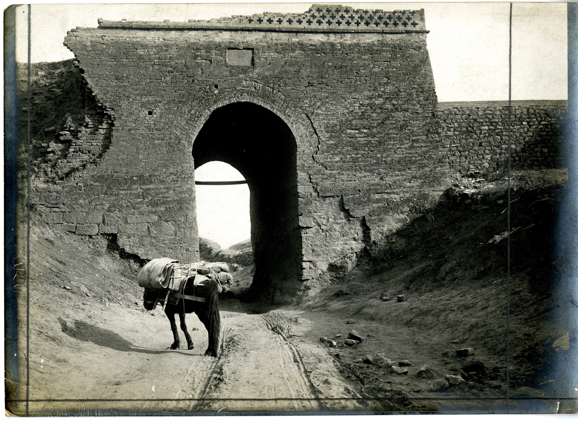 China, Miscellaneous Scenes: Horse loaded with supplies waiting near deteriorating gate