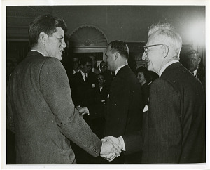 Image of John Fitzgerald Kennedy (left) shaking hands with Joseph H. Kraus