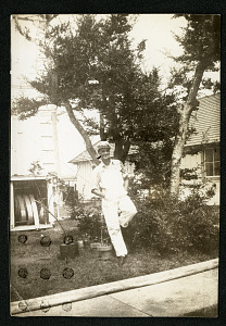 Image of Unidentified Man in Overalls Leaning Against a Tree