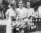 Three women pose with flowers