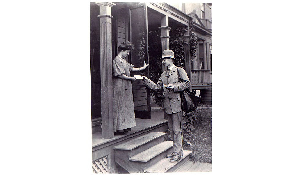 Photograph of letter carrier delivering mail