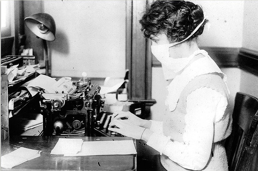 A New York City typist wears a mask to protect herself during the 1918 flu pandemic. Courtesy National Archives and Records Administration, record number 165-WW-269B-16.