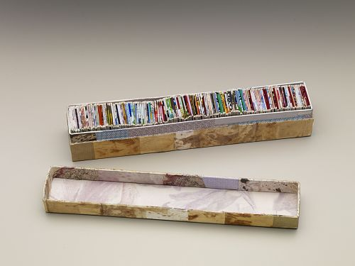 Bits and Pieces by Peter Clarke. South Africa, 2005-2006. African Art Museum artists' books exhibit research image. Depicts a small accordion book made of up different papers compressed into a long, skinny box.