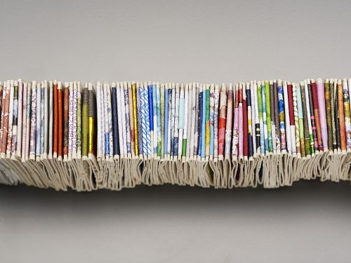 Bits and Pieces by Peter Clarke. South Africa, 2005-2006. African Art Museum artists' books exhibit research image. Detail of the edges of the compressed pages exhibiting a wide assortment of colors and textures.