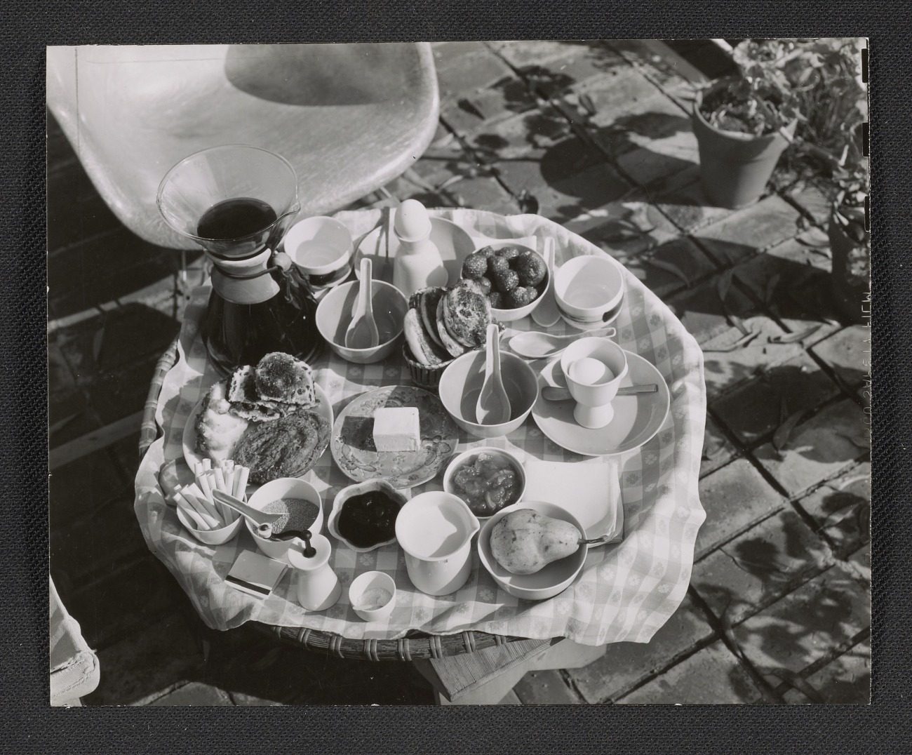Shows a table on the patio at the Eames house set for breakfast, with breads and jam, boiled eggs, fruit, coffee and cigarettes.