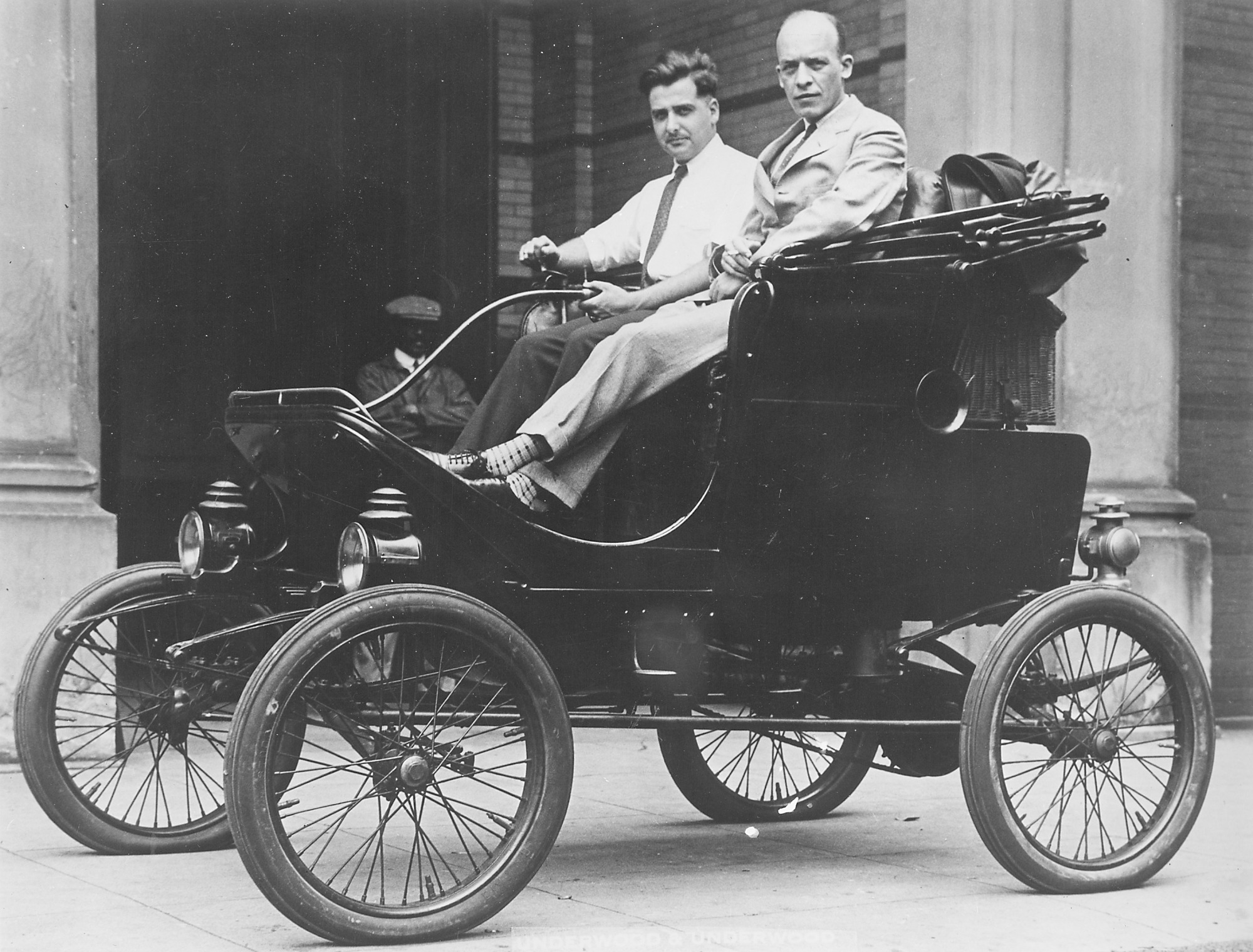 Paul E. Garber (left) poses at the tiller of a White steam automobile