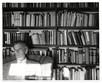 Aldous Huxley seated near bookcases