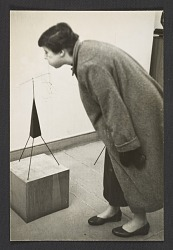Photograph of woman blowing on Alexander Calder sculpture
