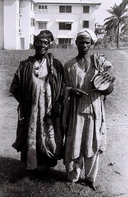 Field Work in Ibadan, Western Region (Nigeria): Elderly Man (probably Yoruba Informant) Accompanied by Musician with Talking Drum, on Campus of University College of Ibadan