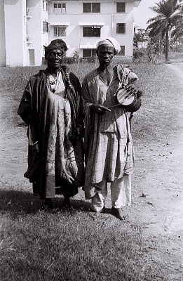 Field Work in Ibadan, Western Region (Nigeria): Elderly Man (probably Yoruba Informant) Accompanied by Musician with Talking Drum, on Campus of University College of Ibadan