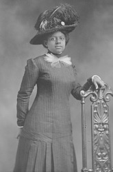 Portrait of African American woman wearing a hat and a pin-stripped dress