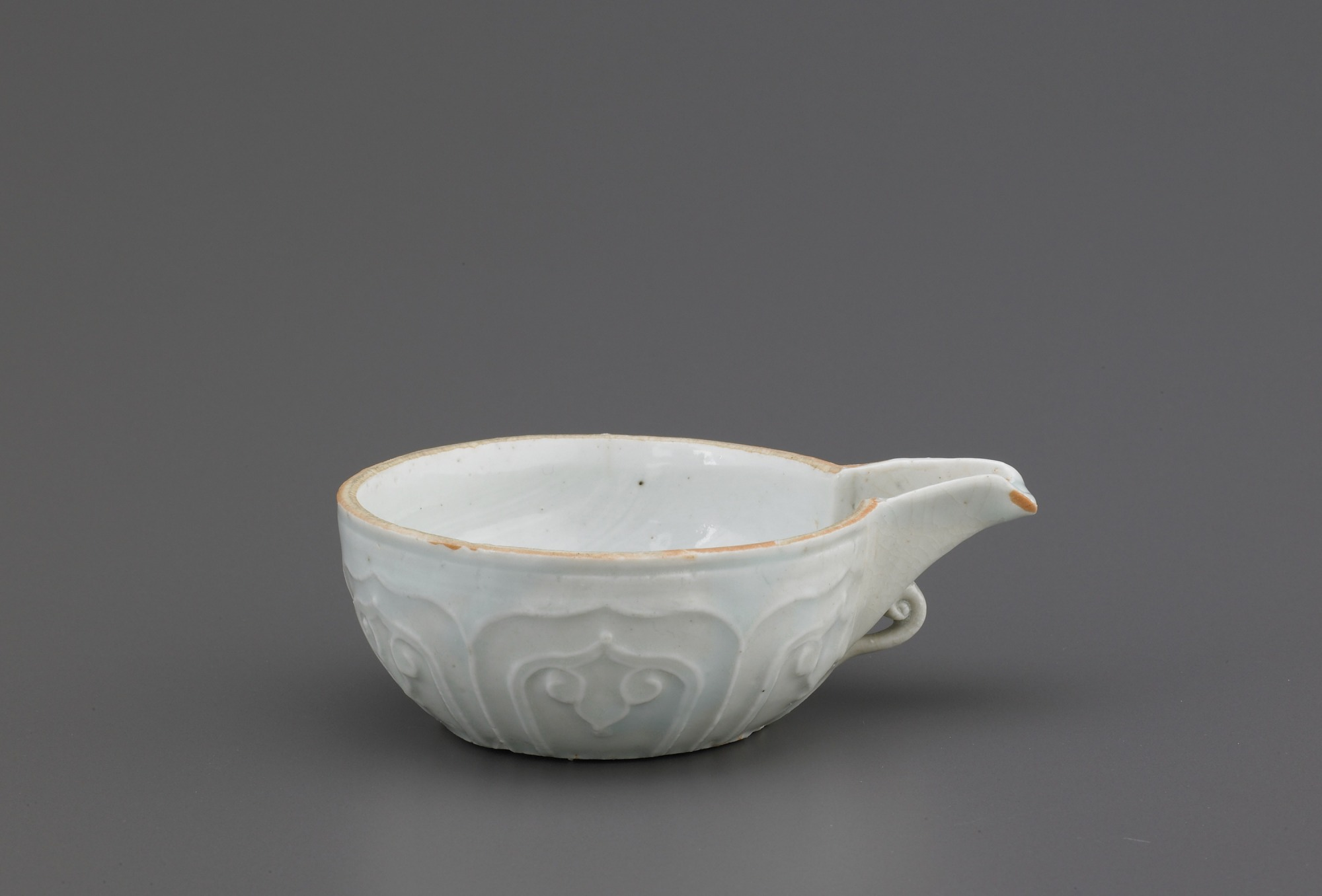 Spouted bowl with molded decoration