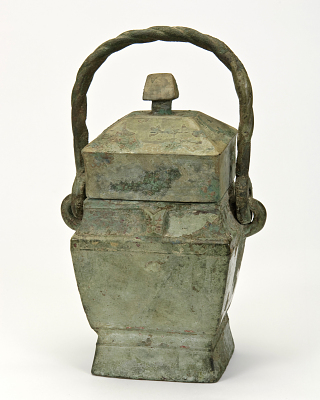 Miniature ritual rectangular lidded wine container (fangyou) with bovine heads; inscribed
