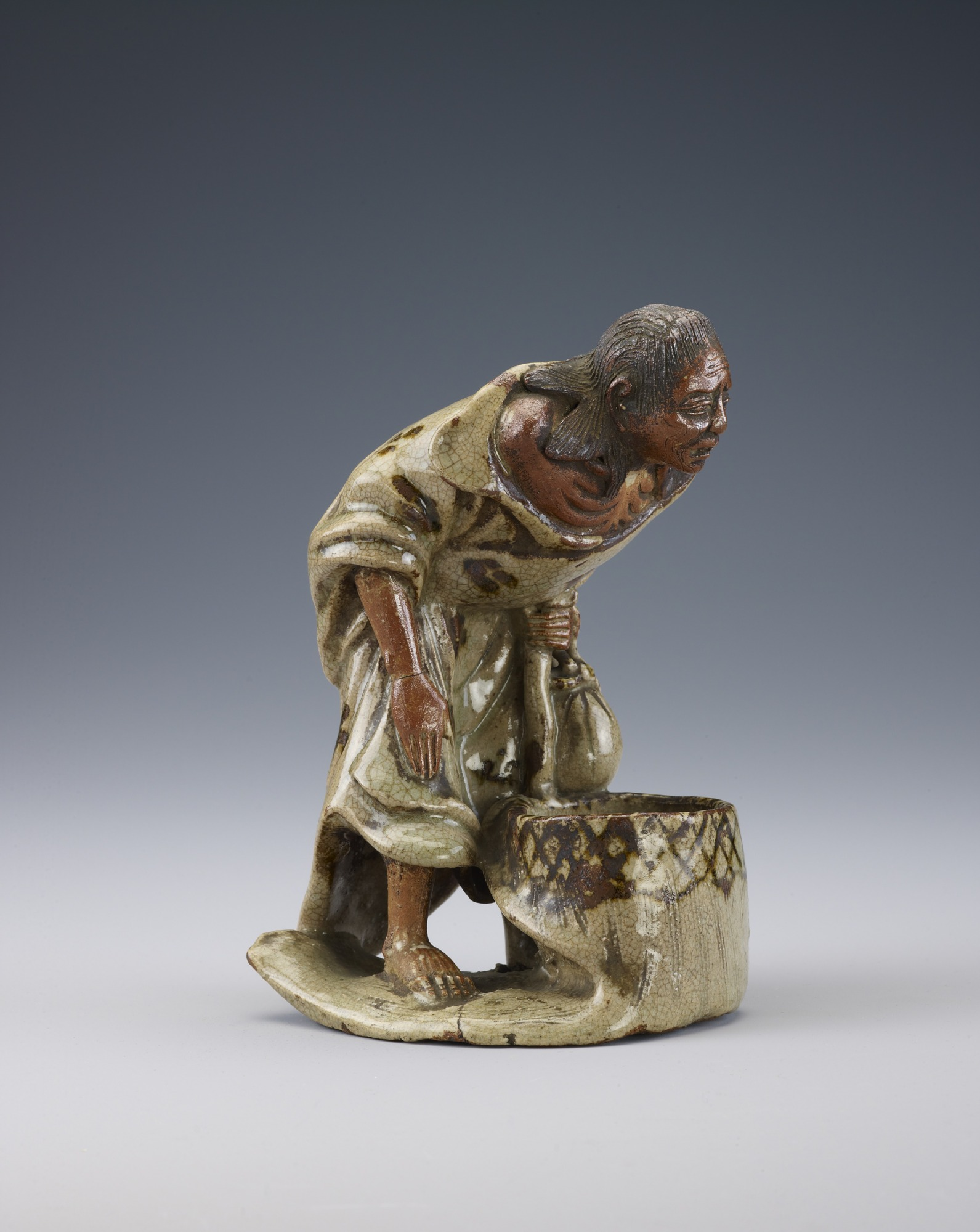 Figure of elderly person in tattered kimono leaning on staff, possibly Sotoba Komachi
