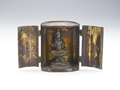 Small figure of a Buddhist deity on a lotus pedestal within a metal case (traveling shrine)